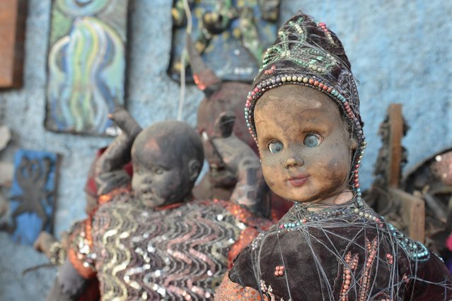 In this April 2, 2016 photo, dusty sculptures made of cast-off baby dolls sit in an open-air museum and art workshop off a trash-strewn street cutting through some of the poorest neighborhoods in Port-au-Prince, Haiti. They were created by Haitian artists called Atis Rezistans who have become celebrated in the international art world by creating sculptures out of scrapped car parts, old wood, discarded toys and even human skulls found scattered outside crumbling mausoleums. (Photo by David McFadden/AP Photo)