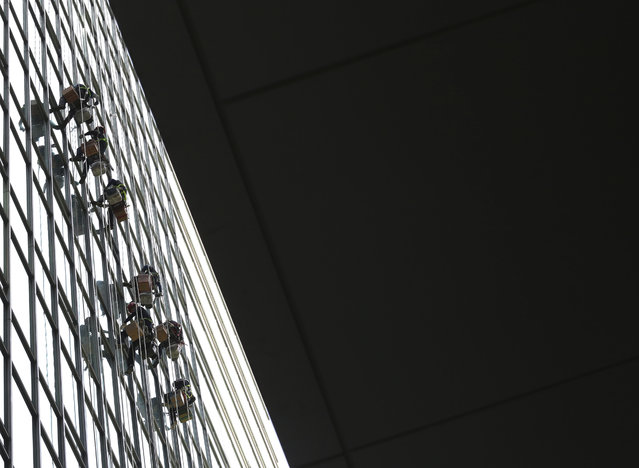 Workers hang on the ropes to attach silicone to windows on a building in Seoul, South Korea, Wednesday, May 29, 2019. (Photo by Ahn Young-joon/AP Photo)