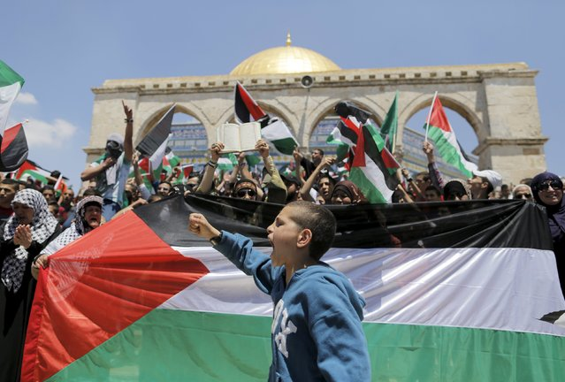 A Palestinian boy shouts slogans as others wave flags after Friday prayers during a protest to mark Nakba day near the Dome of the Rock on the compound known to Muslims as Noble Sanctuary and to Jews as Temple Mount, in Jerusalem's Old City May 15, 2015. (Photo by Ammar Awad/Reuters)