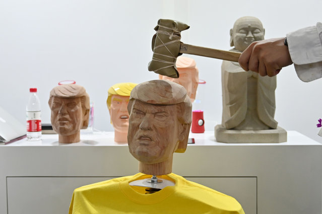 """A man hits a bobble head in the likeness of US President Donald Trump as part of a """"stress relief station"""" from a Japanese company during the Consumer Electronics Show, Ces Asia 2019 in Shanghai on June 11, 2019. (Photo by Héctor Retamal/AFP Photo)"""