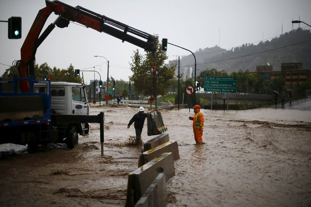 Workers prepare a barrier on a flooded street in Santiago, April 17, 2016. (Photo by Ivan Alvarado/Reuters)