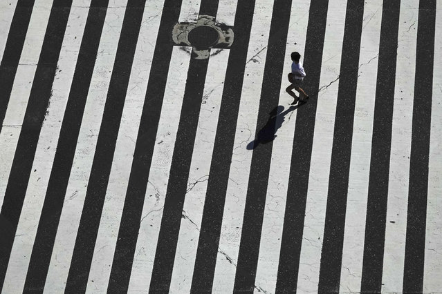 A woman runs across the famous Shibuya crossing Thursday, June 13, 2019, in Tokyo. It's not just a crossing. Located just outside Shibuya Station, the scramble crossing is one of the top tourist attractions in Japan. It's so famous that there's an observation deck on the rooftop of a building built to watch the crossing. During rush hours, an estimated 1000 to 2500 people cross the intersection during each traffic light change. (Photo by Jae C. Hong/AP Photo)