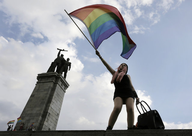 An activist waves a rainbow flag in front of the Monument of the Soviet Army, during the Sofia Gay Pride Parade in Sofia, Saturday, June 27, 2015. Hundreds paraded through the Bulgarian capital of Sofia under rainbow-colored balloons and banners for that city's eighth Gay Pride march on Saturday. They were flanked by police in the wake of calls by some extremist groups to stop the rally. (Photo by Valentina Petrova/AP Photo)