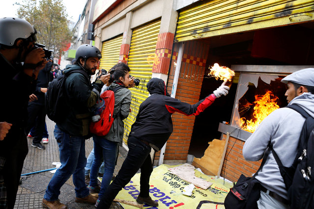 A demonstrator throws a molotov cocktail bomb against a store during a rally commemorating May Day in Santiago, Chile May 1, 2016. (Photo by Ivan Alvarado/Reuters)