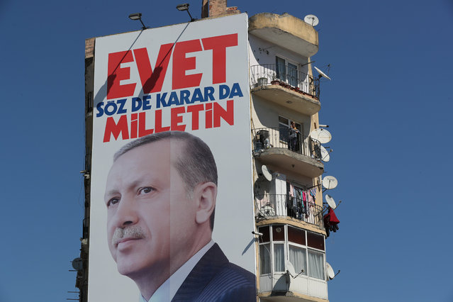A woman stands in her balcony near a giant picture of Turkish President Recep Tayyip Erdogan reading, 'Vote Yes, only public can speak and make decision', in Istanbul, Turkey, 29 March 2017. The Turkish parliament on 21 January approved a reform of the constitution to change the country's parliamentarian system of governance into a presidential one, which the opposition denounced as giving more power to Turkish president Recep Tayyip Erdogan. A referendum on the amendments is expected to be held in April. (Photo by Tolga Bozoglu/EPA)
