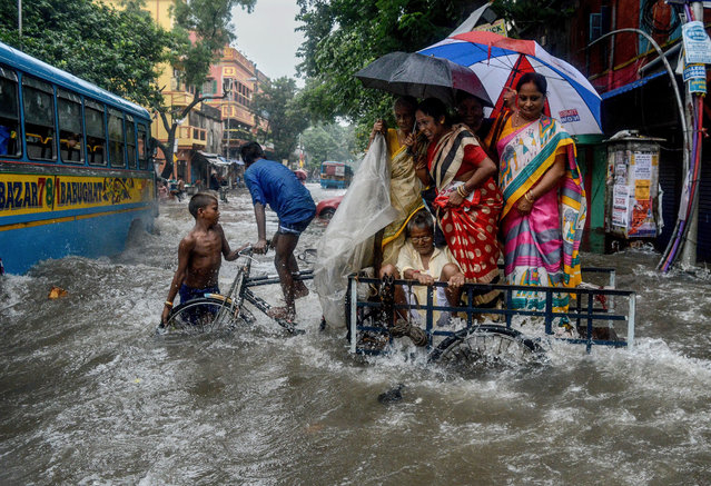 A family tries to cross a flooded road amid gushing water in Kolkata, India on August 17, 2019. Heavy rain continues for a second day in Kolkata, which contuinued to flood many streets all around the city. Authorities are working overtime to clear the roads. (Photo by  Debarchan Chatterjee/Zuma Wire/Rex Features/Shutterstock)
