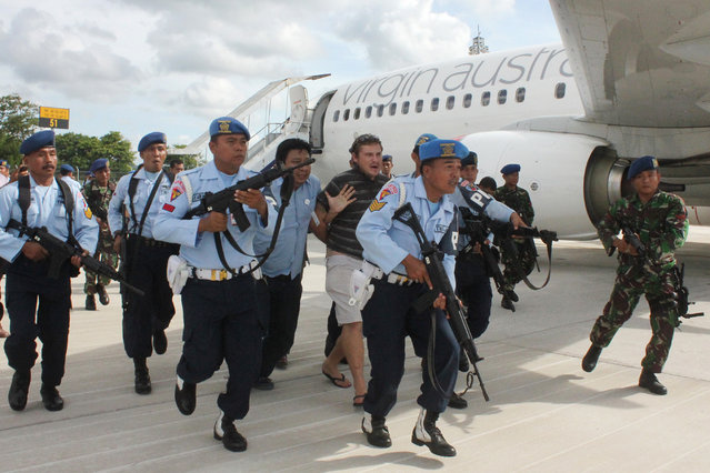 A handout picture provided by the Indonesian Air Force shows Australian Matt Christopher (C) is escorted away by Indonesian military officers at Ngurah Rai International Airport in Bali, Indonesia, 25 April 2014. An unruly passenger and not a hijack caused a Virgin Australia passenger jet to report a problem when it landed at Denpasar airport in Bali, the airline said on 25 April 2014.  (Photo by EPA/HO)