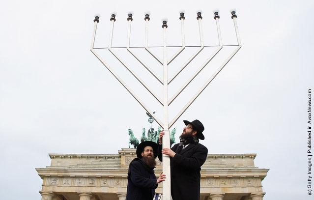 Rabbis Yehuda Teichtal (L) and Schmuel Segal pray as they erect a large nine-armed candleholder, a Hannoukiah, or Menorah, ahead of the start of the eight-day-long and annual Jewish Festival of Lights known as Chanukah, in front of the Brandenburg Gate