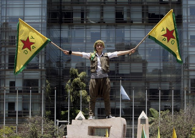 A Kurdish girl who lives in Lebanon waves flags of the Kurdish People's Protection Units, also known as YPG, during a demonstration in solidarity with their Kurdish brethren in northern Syria who are fighting against Islamic State group militants, in front of the United Nations headquarters in Beirut, Lebanon, Sunday, July 5, 2015. (Photo by Bilal Hussein/AP Photo)