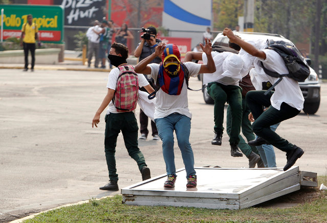Students stomp on a billboard during a protest to demand the government to repeal a law that requires high school seniors to teach at least two people to read and write, as part of a graduation programme in Tegucigalpa, Honduras, May 4, 2016. (Photo by Jorge Cabrera/Reuters)