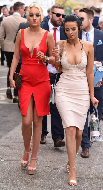 Two women dress to impress in a lovely red dress and tight-fitting nude number during the Grand National Festival at Aintree Racecourse on April 7, 2017 in Liverpool, England. (Photo by Fortitude Press)