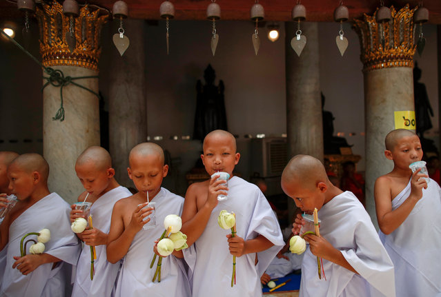 Newly ordained young hill tribe Buddhist novice monks sip water during a mass Buddhist monk ordination ceremony for hill tribe men at Wat Benchamabophit, also known as the Marble Temple in Bangkok, Thailand, 14 July 2019. A total of 168 hill tribe men including young boys were to be ordained as Buddhist monks and novices in the annual mass ordination ceremony to mark the three-month Buddhist Lent which this year begins on 17 July. For the duration of the Buddhist Lent, monks remain in one location, typically in a monastery or on temple grounds, where they engage in meditation and prayer, while laypeople choose to observe Lent by giving up meat, alcohol, and perform other ascetic practices. In Thailand, a Buddhist man is expected to become a monk during some period of his life. (Photo by Rungroj Yongrit/EPA/EFE)