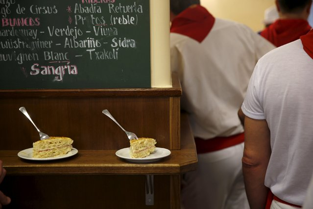 Two pintxos, which are food snacks eaten at bars, lie untouched as revellers watch the first running of the bulls of the San Fermin festival at a bar in Pamplona, northern Spain, July 7, 2015. (Photo by Susana Vera/Reuters)