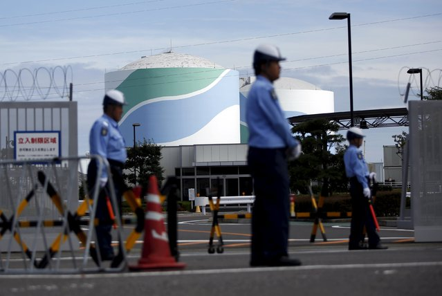 Security officers stand guard in front of an entrance gate of Kyushu Electric Power's Sendai nuclear power station in Satsumasendai, Kagoshima prefecture, Japan, July 8, 2015. Kyushu Electric Power Co started loading uranium fuel rods into a reactor on Tuesday, marking the first attempt to reboot Japan's nuclear industry in nearly two years after the sector was shutdown following the 2011 Fukushima disaster. (Photo by Issei Kato/Reuters)