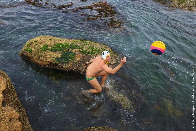 Rob Maitland of Australia collects a ball from the ocean during warm-up for the Water Polo by the Sea match between Australia and the United States of America at at Bondi Icebergs on Bondi Beach