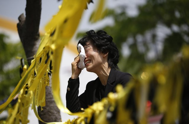 A mourner cries next to yellow ribbons dedicated to missing and dead passengers of sunken passenger ship Sewol, after paying tribute at the official memorial altar in Ansan May 2, 2014. A culture of cosy personal ties that can blur the lines between businesses and those regulating them, of profit over safety, and soft courts is in focus as South Korea demands answers over the sinking of the ferry with the loss of more than 300 lives, mainly high school students. (Photo by Kim Hong-Ji/Reuters)