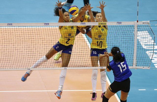 Thailand's Malika Kanthong spikes against Brazil's players Juciely, left, and Gabi during their women's World Grand Prix volleyball match in Sao Paulo, Brazil, Saturday, July 11, 2015. (Photo by Andre Penner/AP Photo)