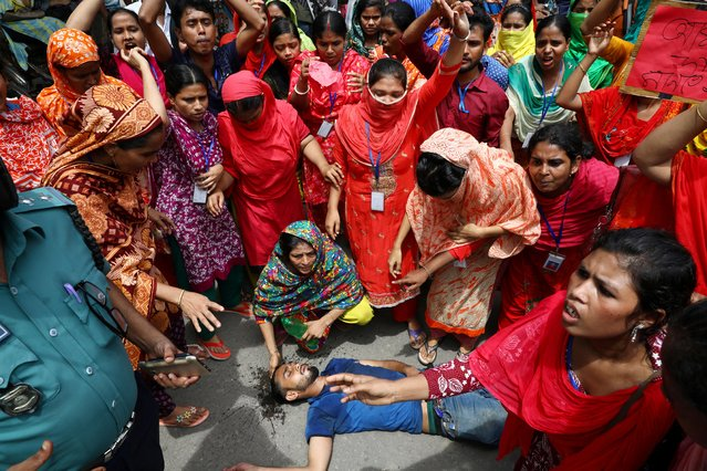 An injured garment worker lies on the ground during clashes with police at a protest demanding for arrears in Dhaka, Bangladesh, September 12, 2019. (Photo by Mohammad Ponir Hossain/Reuters)
