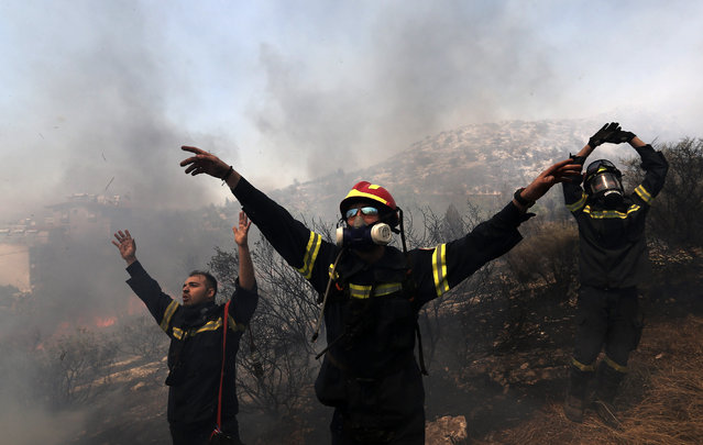 Firefighters give directions at an helicopter on the mountain of Ymittos in Athens, Friday, July 17, 2015. Greek firefighters battled large brush and forest fires on the outskirts of Athens and in the country's southern Peloponnese region Friday, where flames forced the evacuation of at least three villages and two summer camps. (Photo by Giannis Liakos/InTime News via AP Photo)