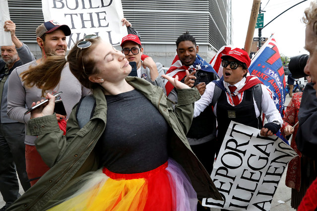 An anti-Trump demonstrator (L) interacts with pro-Trump supporters near the Intrepid Sea, Air & Space Museum ahead of an expected visit by U.S. President Donald Trump in the Manhattan borough of New York City, U.S., May 4, 2017. (Photo by Brendan McDermid/Reuters)