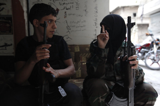"A female member of the ""Mother Aisha"" batallion gestures as she holds a weapon in Aleppo's Salaheddine district, September 19, 2013. (Photo by Loubna Mrie/Reuters)"