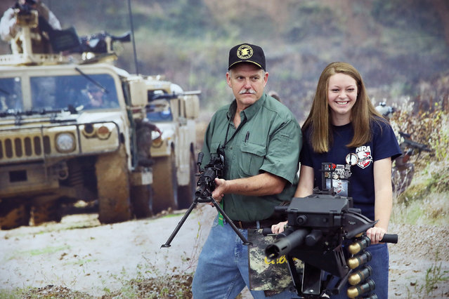 Ernest Belcher poses for a picture with an FN MK 48 machine gun while his daughter Morgan poses with a MK 19 grenade launcher at the NRA Annual Meetings & Exhibits on May 21, 2016 in Louisville, Kentucky. (Photo by Scott Olson/Getty Images)