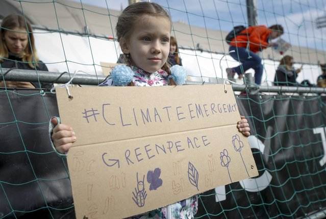 A girl holds a poster in front of the Russian government's building during a protest flash mob of Greenpeace for climate protection in Moscow, Russia, Friday, September 27, 2019. (Photo by Dmitri Lovetsky/AP Photo)