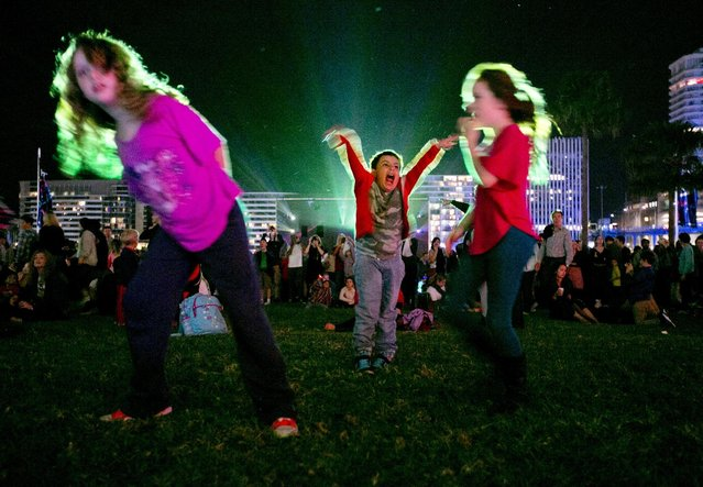 Children dance to a colourful pattern projected onto the wall of Museum of Contemporary Art on the second night of the Vivid Sydney light and music festival May 24, 2014. For 18 days beginning on Friday the Vivid Sydney festival will combine outdoor lighting sculptures and installations and is one of the world's largest creative industry forums. (Photo by Jason Reed/Reuters)