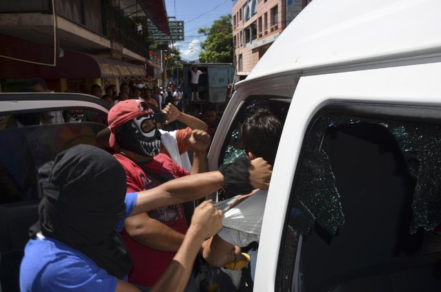 Masked men try to pull out a tax driver from his vehicle after rival taxi unions fighting for permits clashed in the city of Chilpancingo, Mexico, Monday, July 20, 2015. (Photo by Alejandrino Gonzalez/AP Photo)