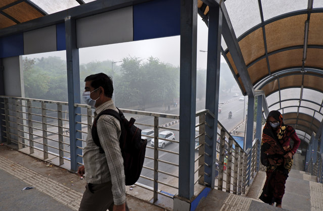 "In this Sunday, November 3, 2019, photo, Indians wear pollution mask and cross over a pedestrian bridge amidst thick layer of smog in New Delhi, India. Authorities in New Delhi are restricting the use of private vehicles on the roads under an ""odd-even"" scheme based on license plates to control vehicular pollution as the national capital continues to gasp under toxic smog. (Photo by Manish Swarup/AP Photo)"