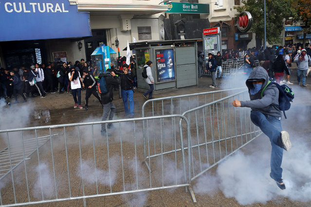 A demonstrator attempts to kick a tear gas canister during an unauthorized march called by secondary students to protest against government education reforms in Santiago, Chile, May 26, 2016. (Photo by Ivan Alvarado/Reuters)