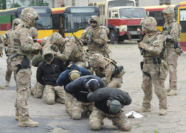 """Members of the Polish Army military police anti terrorist squad train detaining """"hijackers"""", at a bus depot in Warsaw, Poland, Tuesday, May 31, 2016. The excercise was a part of preparations for the upcoming NATO summit in Warsaw in July. (Photo by Alik Keplicz/AP Photo)"""