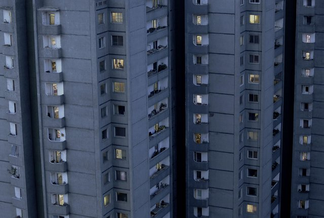 Lights are switched on in occupied apartments as dusk descends in Pyongyang, North Korea on Sunday, May 10, 2015. Majority of North Koreans live in high-rise apartments in Pyongyang. (Photo by Wong Maye-E/AP Photo)