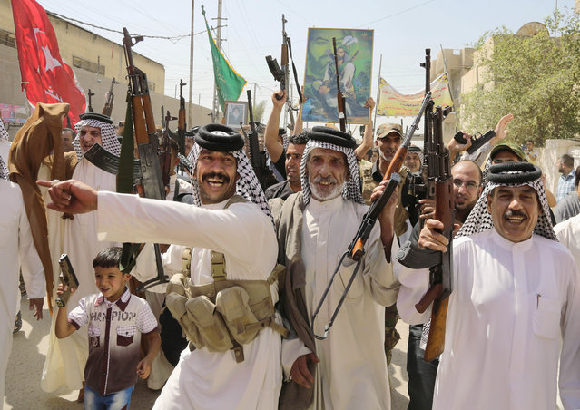 Iraqi Shiite tribal fighters raise their weapons while chanting slogans against the al-Qaida inspired Islamic State of Iraq and the Levant (ISIL), in Baghdad's Sadr city, Saturday, June 14, 2014, after authorities urged Iraqis to help battle insurgents. (Photo by Karim Kadim/AP Photo)