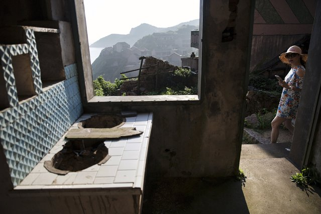 A tourist looks inside a house in the abandoned fishing village of Houtouwan on the island of Shengshan July 26, 2015. (Photo by Damir Sagolj/Reuters)