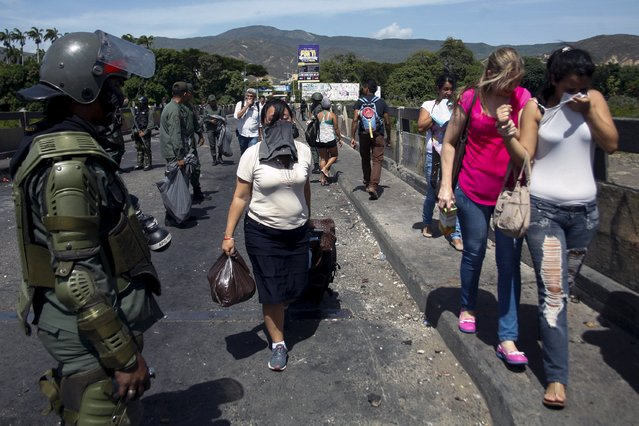 People cover their faces to protect themselves from the tear gas, as they walk after clashes between Venezuela's National Guards and protesters at Simon Bolivar international bridge, on the border with Colombia, at San Antonio in Tachira state, Venezuela July 29, 2015. Demonstrators clashed with the Venezuelan National Guard on Wednesday at the  Colombian-Venezuelan border, due to the death of a man who was illegally bringing products back and forth between the two countries, according to local media. (Photo by Carlos Eduardo Ramirez/Reuters)