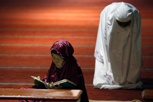 A Muslim woman (L) reads the Koran as other pray during the first day of the holy fasting month of Ramadan at Istiqlal mosque in Jakarta, Indonesia June 6, 2016. (Photo by Reuters/Beawiharta)