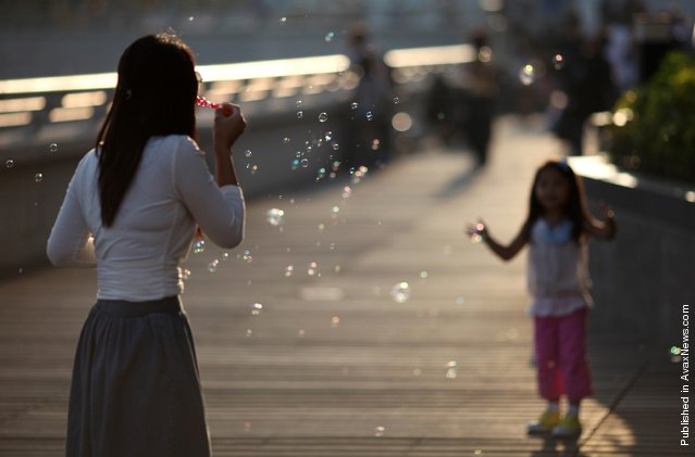 A woman blows bubbles toward a child on a sunny afternoon in Hong Kong on April 9, 2011