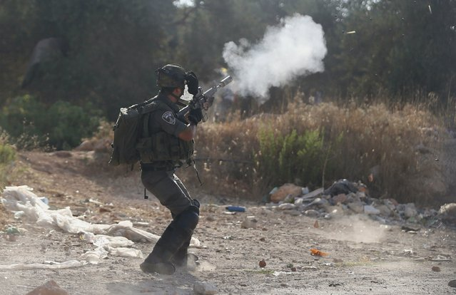 An Israeli border policeman fires a tear gas canister towards Palestinians during clashes following the funeral of Palestinian youth Laith al-Khaldi, in Jalazoun refugee camp near the West Bank city of Ramallah August 1, 2015. (Photo by Mohamad Torokman/Reuters)