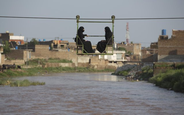 Pakistani women sit in a trolley crossing a stream flooded due to heavy rains in Rawalpindi, Pakistan, Wednesday, July 22, 2015. Pakistan's military deployed helicopters and boats Wednesday to evacuate flood victims from the country's north, where monsoon rains and flash floods washed away several villages earlier in the week. (Photo by Mohammad Sajjad/AP Photo)