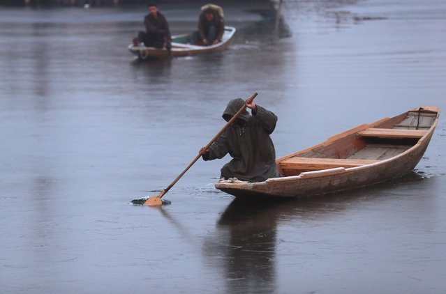 A man uses his oar to break ice to move his boat on the partially frozen Dal Lake on a cold winter morning in Srinagar on December 30, 2019. (Photo by Danish Ismail/Reuters)