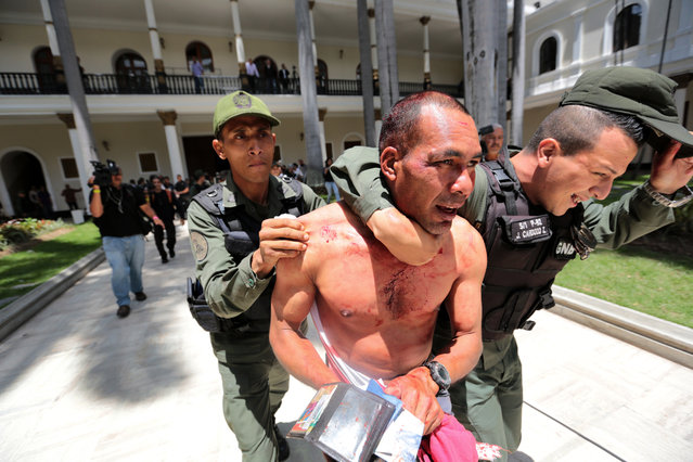 A supposed government supporter who was part of a group that tried to force its way into the National Assembly, is temporarily detained by national guardsmen, but let go soon after, in Caracas, Venezuela, Wednesday, July 5, 2017. Pro-government militias wielding wooden sticks and metal bars violently stormed congress and began attacking opposition lawmakers at the end of a special session coinciding with Venezuela's independence day. (Photo by Fernando Llano/AP Photo)