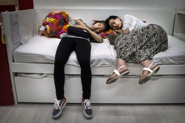 Chinese shoppers sleep on a bed in the showroom of the IKEA store on July 6, 2014 in Beijing, China. Of the world's ten biggest Ikea stores, 8 of them are in China to cater to the country's growing middle class. The stores are designed with extra room displays given the tendency for customers to make a visit an all-day affair. Store management does not discourage shoppers from sleeping on Ikea furniture, even marking them with signs inviting customers to try them out. (Photo by Kevin Frayer/Getty Images)