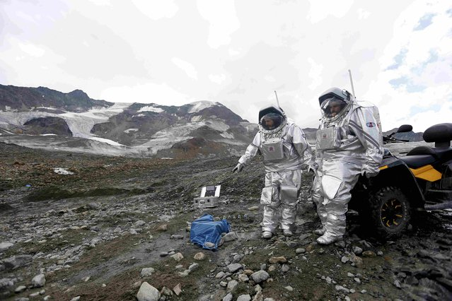 Stefan Dobrovolny of Austria and Inigo Munoz Elorza of Spain (R) stand in front of a quad bike during a simulated Mars mission on Tyrolean glaciers in Kaunertal, Austria, August 7, 2015. The Austrian Space Forum is sending some of its researchers to practice weight-less walking in spacesuits on a glacier which resembles the terrain on Mars. (Photo by Dominic Ebenbichler/Reuters)