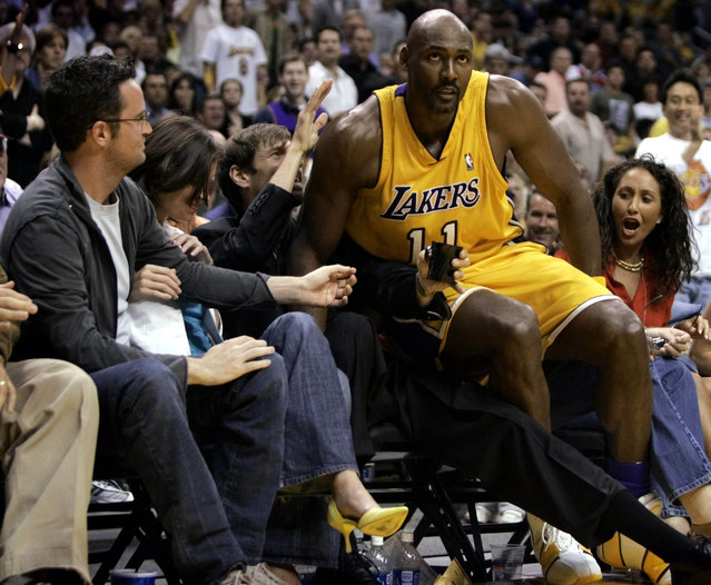 Los Angeles Lakers forward Karl Malone falls into the crowd next to Mathew Perry in Los Angeles, May 2004. (Photo by Mike Blake/Reuters)