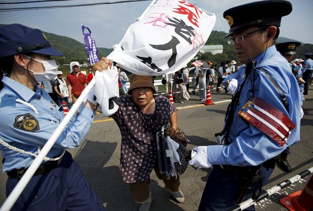 A protester is stopped by police officers during a march against the restarting of the plant in front of an entrance of Kyushu Electric Power's Sendai nuclear power station in Satsumasendai, Kagoshima prefecture, Japan, August 9, 2015. Japan is due to switch on a nuclear reactor for the first time in nearly two years as Prime Minister Shinzo Abe seeks to reassure a nervous public that tougher standards mean the sector is now safe after the Fukushima disaster in 2011. (Photo by Issei Kato/Reuters)