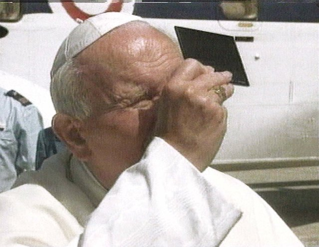 Pope John Paul II watches the eclipse through a piece of special glass at Castel Gandolfo, the papal summer retreat in the hills southeast of Rome, in this image taken from television Wednesday August 11 1999. The pope kept his Vatican weekly audience with pilgrims short, then flew to Castel Gandolfo where he could see about 84 percent of the total coverage. (Photo by AP Photo/APTN)