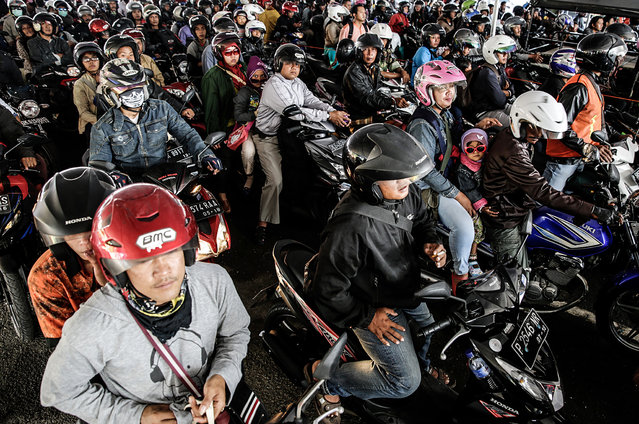 Indonesian riders on their motorbikes queue to board a ferry at Gilimanuk Port on July 24, 2014 in Jembrana, Indonesia.  In the days ahead of the Eid al Fitr holiday, millions of Indonesians working in Bali return to their hometowns to celebrate the holiday with family. (Photo by Agung Parameswara/Getty Images)