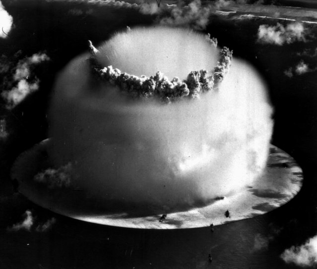 """A huge mushroom cloud rises above Bikini atoll in the Marshall Islands July 25, 1946 following an atomic test blast, part of the U.S. military's """"Operation Crossroads"""". The dark spots in foreground are ships that were placed near the blast site to test what an atom bomb would do to a fleet of warships. (Photo by AP Photo)"""