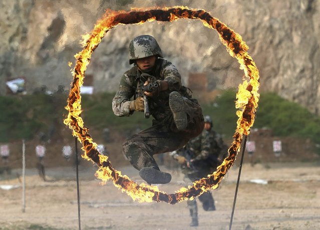 A member of People's Liberation Army (PLA) coastal defence force jumps through a burning obstacle during a drill to mark the 87th Army Day at a military base in Qingdao, Shandong province July 29, 2014. The PLA Army Day falls on August 1 every year. Chinese President Xi Jinping has pledged to strike hard against graft in the military, urging soldiers to banish corrupt practices and ensure their loyalty to the ruling Communist Party, state media reported on Friday. (Photo by Reuters/Stringer)